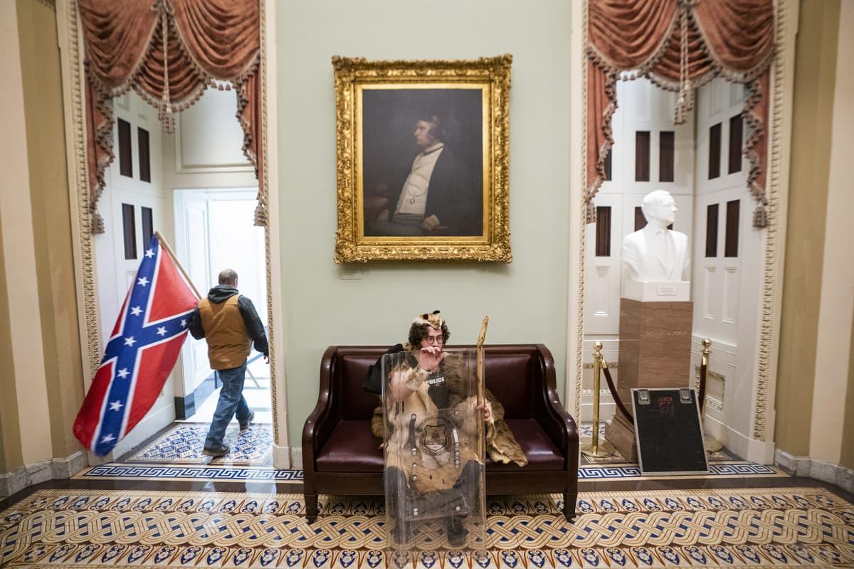 Mielenosoittaja istuu sohvalla Yhdysvaltain kongressitalossa Washington DC:ssä.