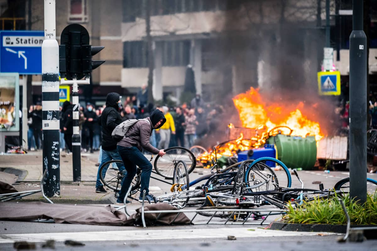 Hollannissa mellakoitiin koronarajoituksia vastaan. Polkupyöriä rikotaan ja taustalla poltetaan jotain.