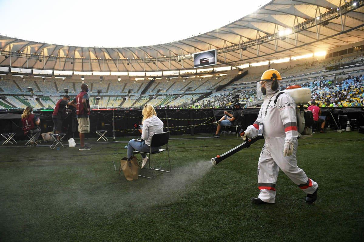 Suojavarusteisiin pukeutunut työntekijä desinfioi stadionin nurmikkoa.