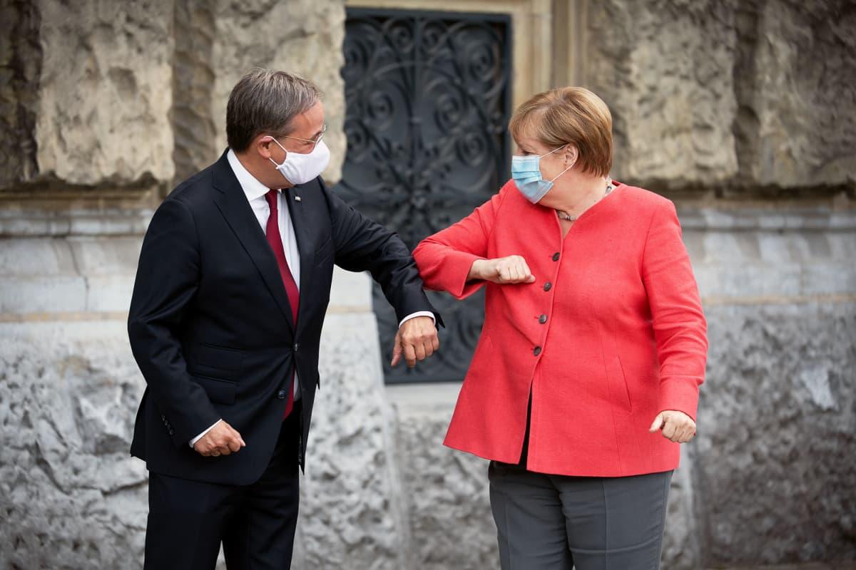 KAsvomaskeihin pukeutuneet Armin Laschet ja Angela Merkel kyynärtervehtivät toisiaan.