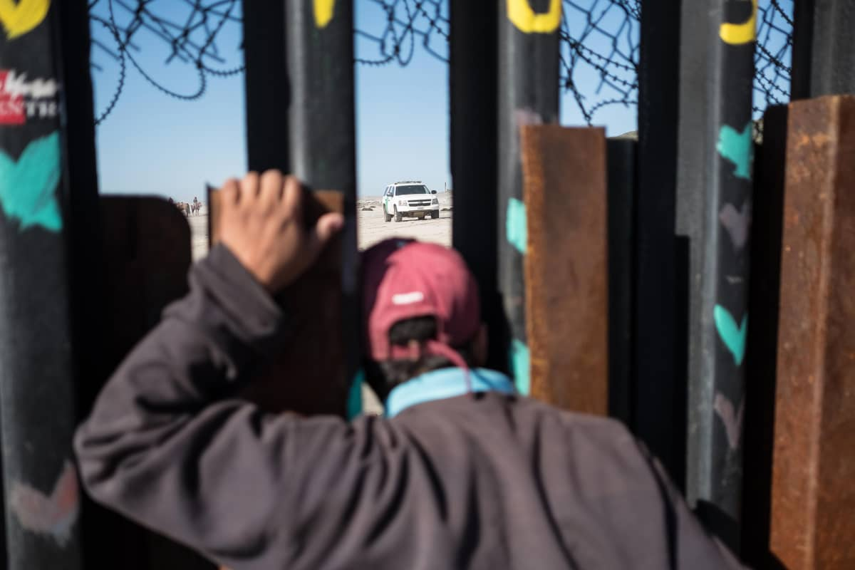 Poika Meksikossa katsoo aidan läpi Yhdysvaltain puolelle ja seuraa rajavartioston  liikkumista.