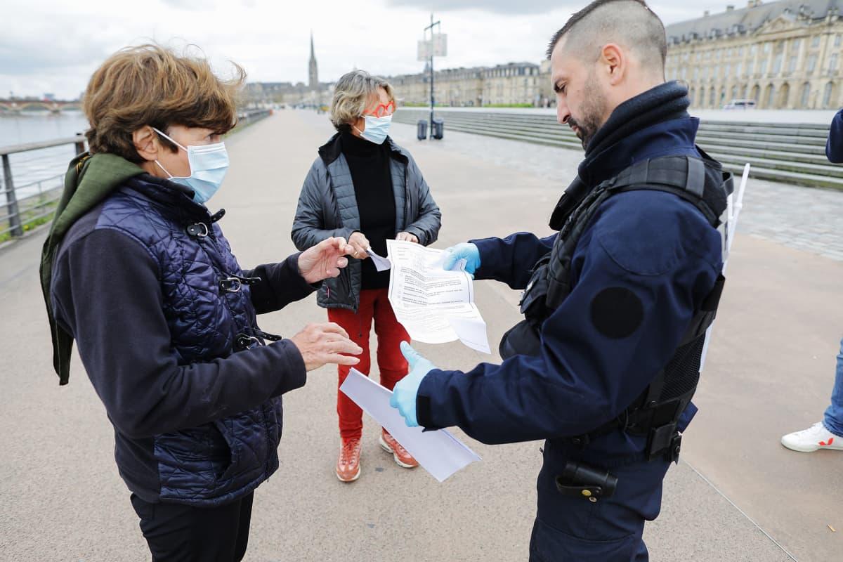 Poliisi tarkastaa kulkijoiden papereita Ranskassa keväällä 2020.