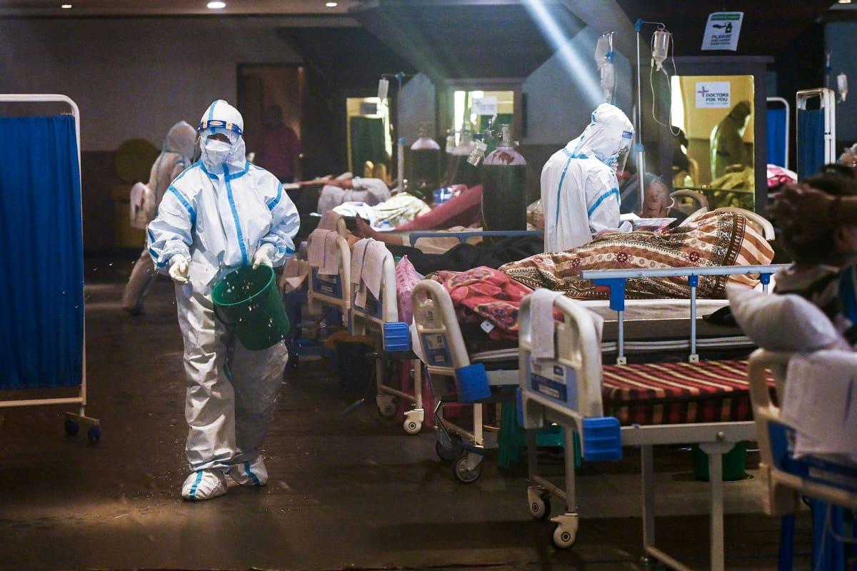 Suojavarusteisiin pukeutuneet työntekijät hoitavat sairaalasängyissä makaavia potilaita.