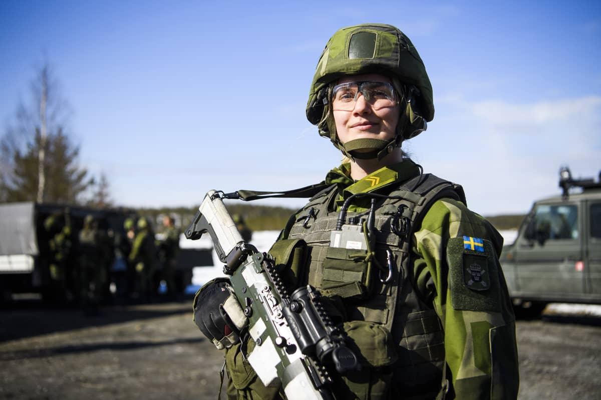 armeija, sotilas Alva Dismo katsoo kameraan taisteluvarustuksessa.