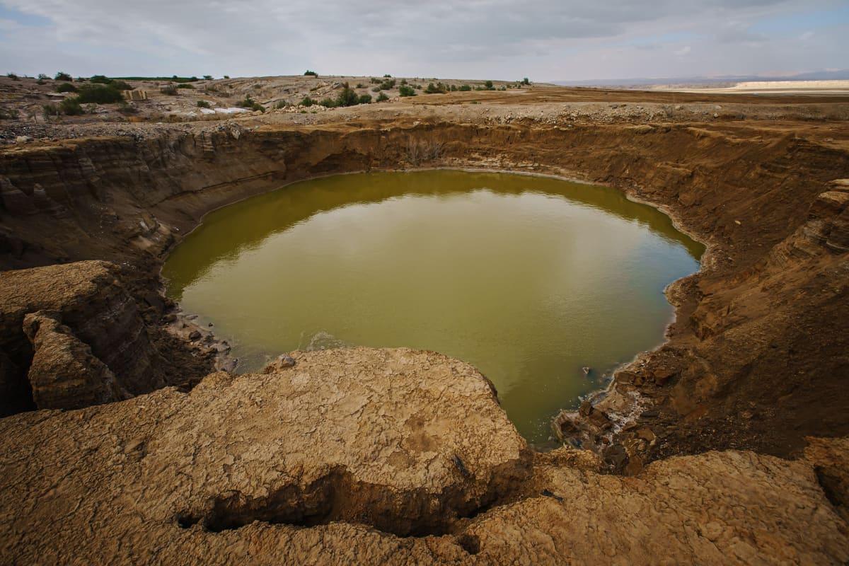 Veden täyttämä sortumakaivo Jordaniassa.