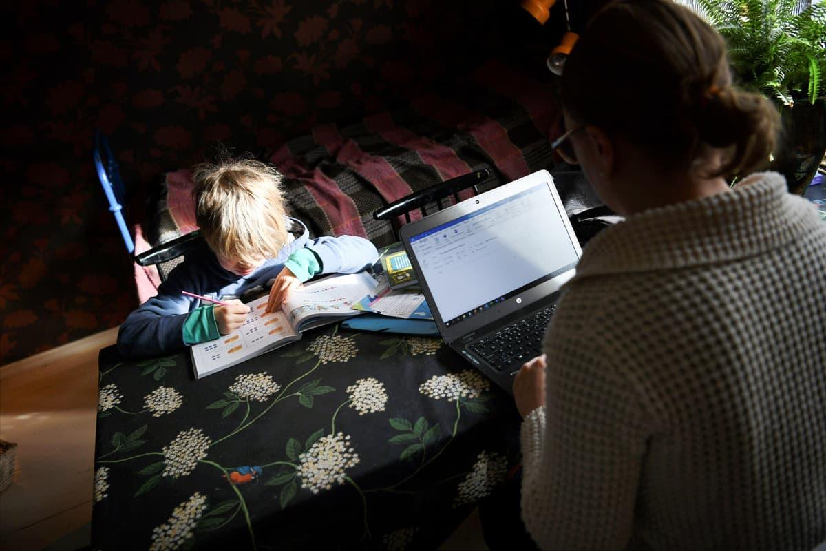 Koulusta kotiin jäänyt lapsi opiskelee yhdessä etätöitä tekevän äidin kanssa kotonaan.