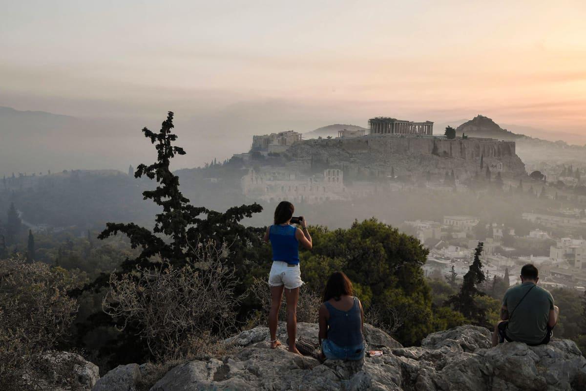 Ihmiset ottavat kuvia Ateenan yllä leijailevasta savusta.