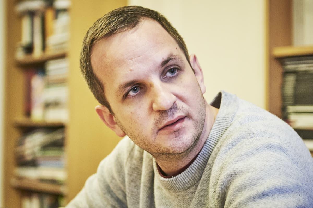 Balázs Tóth harmaassa villapaidassa, taustalla näkyy kirjahyllyjä.