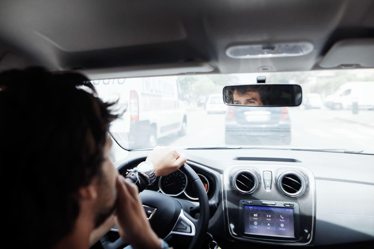 Mies autossa, silmät näkyvät peilistä.