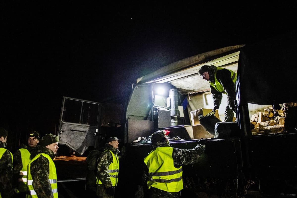 Varusmiehet leiriytyivät Lohjan Kasvihuoneilmiön läheisyyteen ja valmistautuivat avustamaan poliisia. Kuvassa puretaan varusteita autosta.