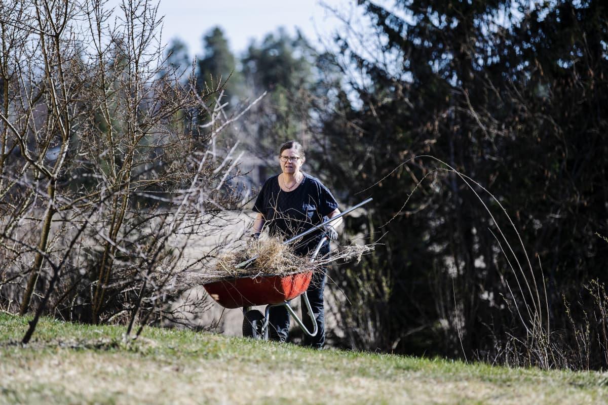Kuvassa Tiia Kylänpää tekee kevättöitä kotipuutarhassaan.