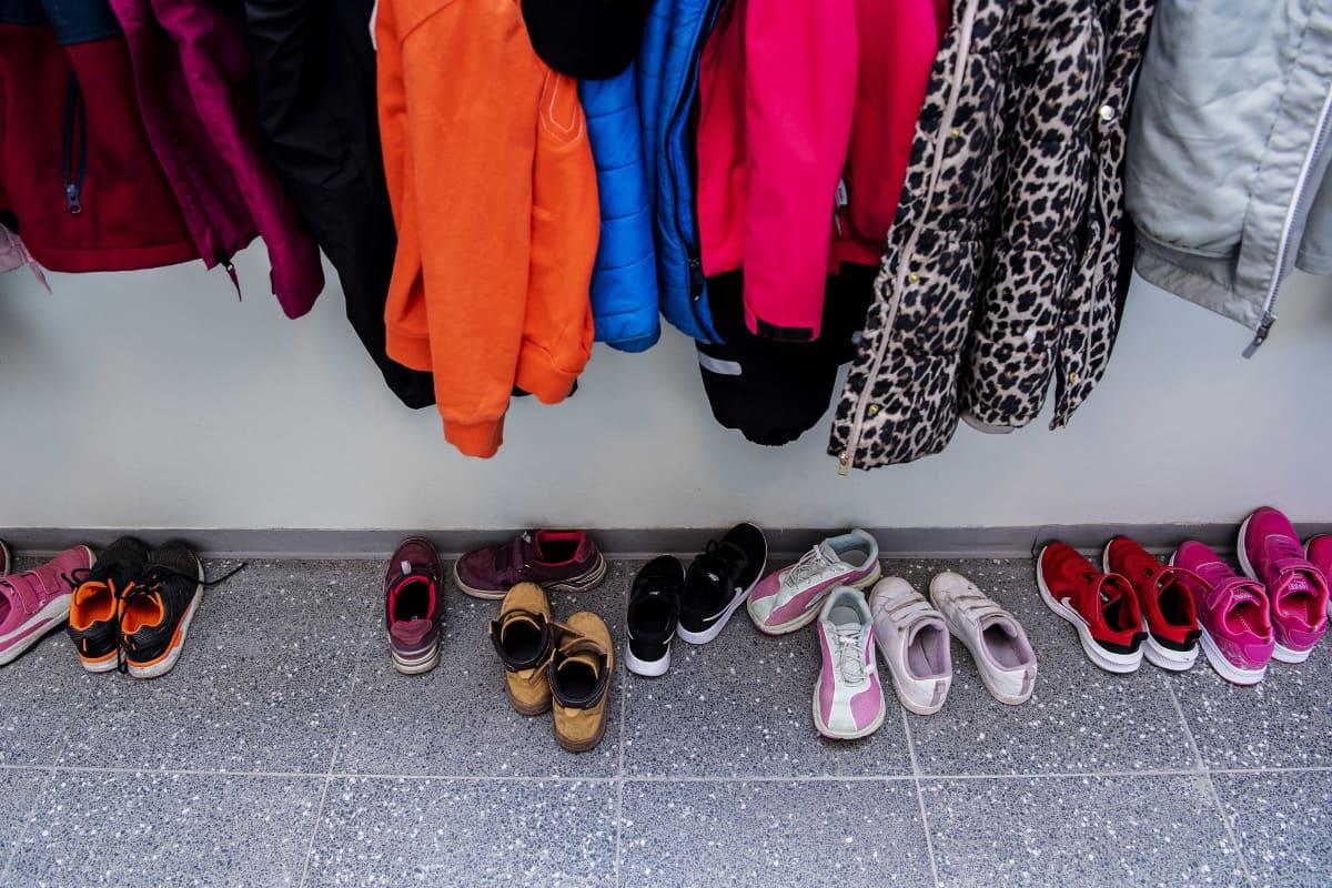 Kuvassa on koululaisten vaatteita naulakossa.