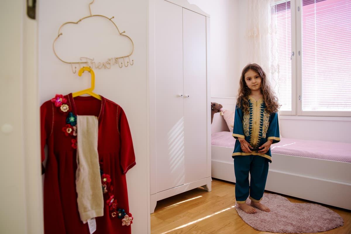 Liliya poseeraa huoneessaan, vasemmalla odottavat huomisen juhlapäivän vaatteet.