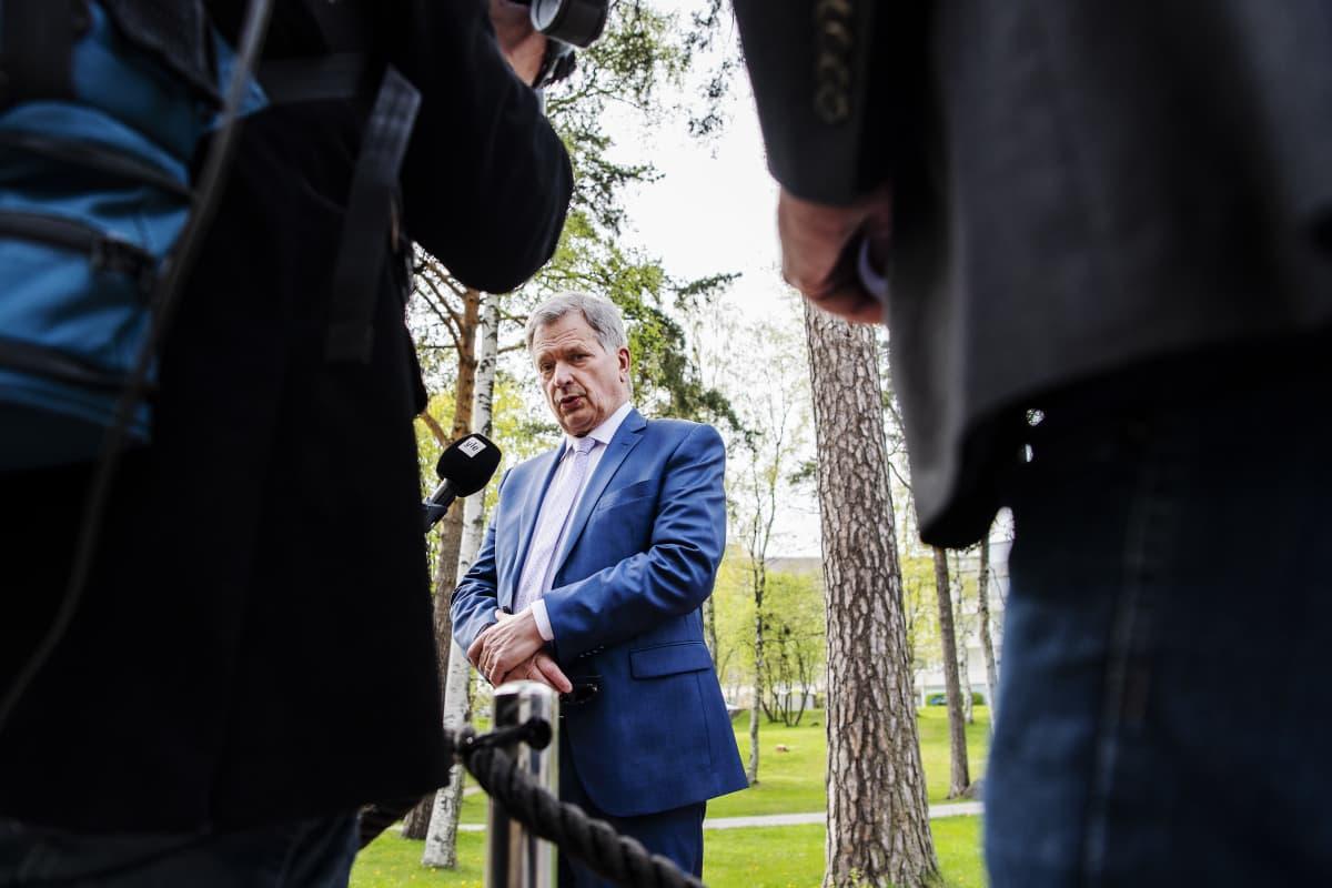Sauli Niinistö puhuu toimittajille ulkona. Niinistöllä on sininen puku ja vaalea kravatti. Kuva on otettu alaviistosta kahden toimittajan takaa. He rajaavat Niinistön kuvan keskelle. Niinistön edessä on Ylen mikrofoni.