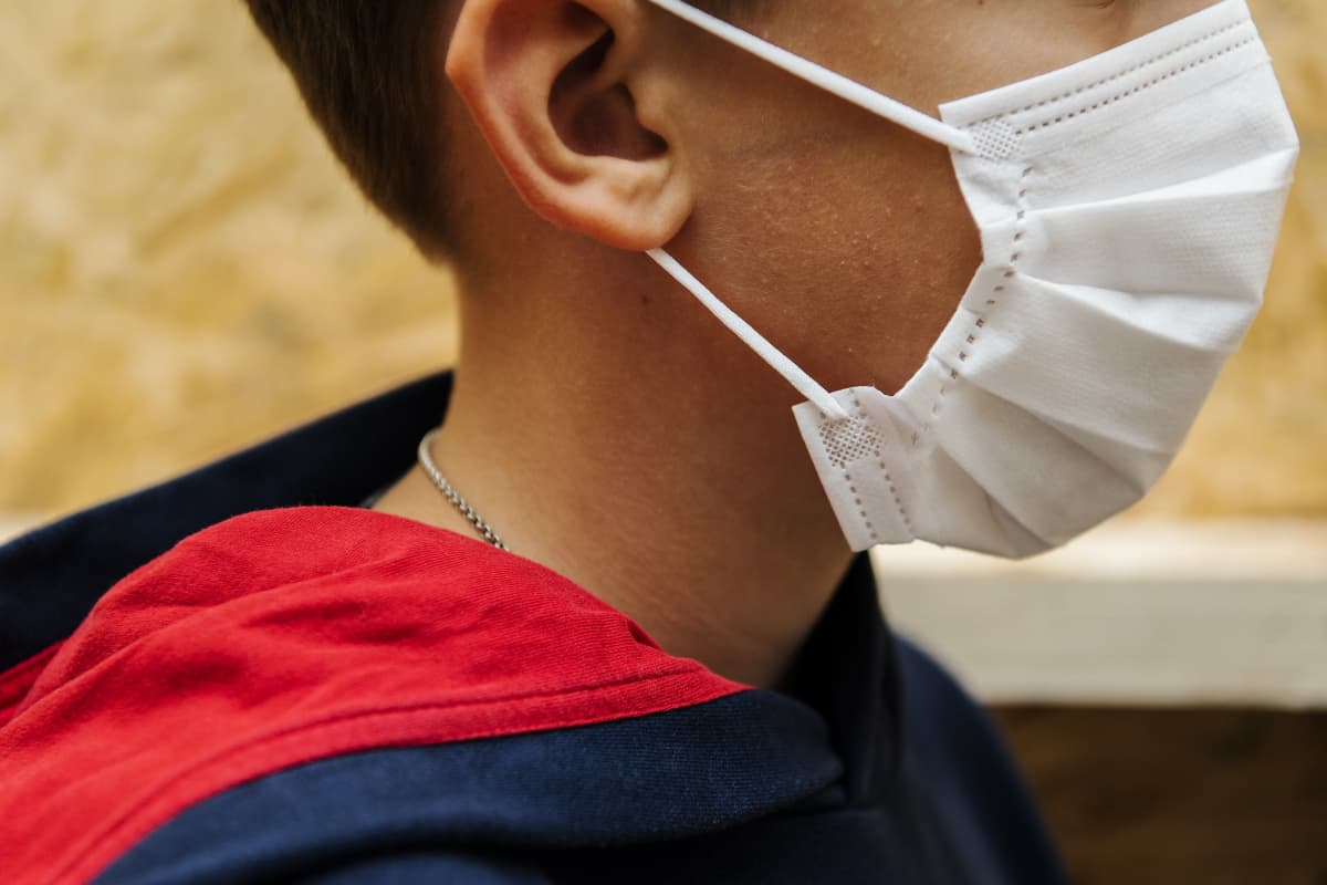 Kuvassa on 10-vuotias poika, jolla on kasvoillaan hengityssuojain.