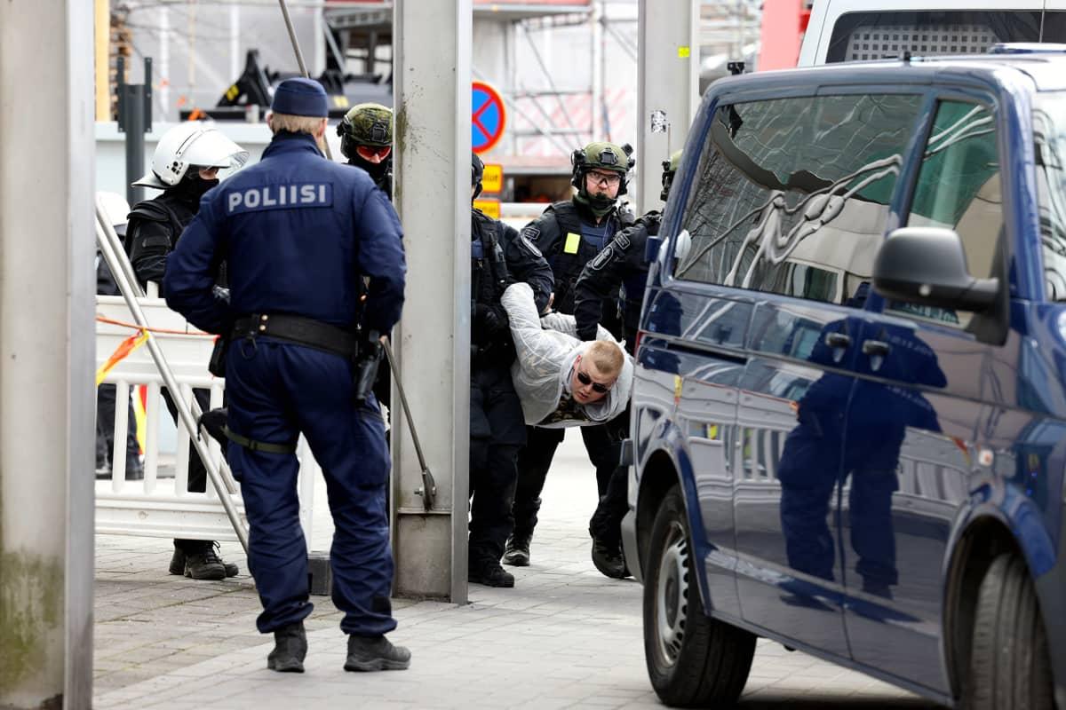Poliisi pidättää mielenosoittajan.