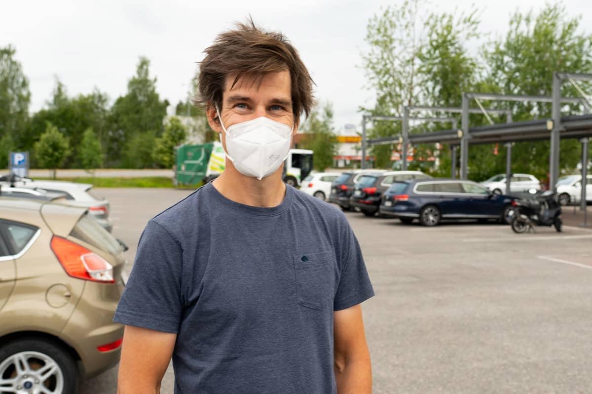 Nuoehko mies sinisessä t-paidassa ja maski kasvoilla kauppakeskuksen parkkipaikalla.