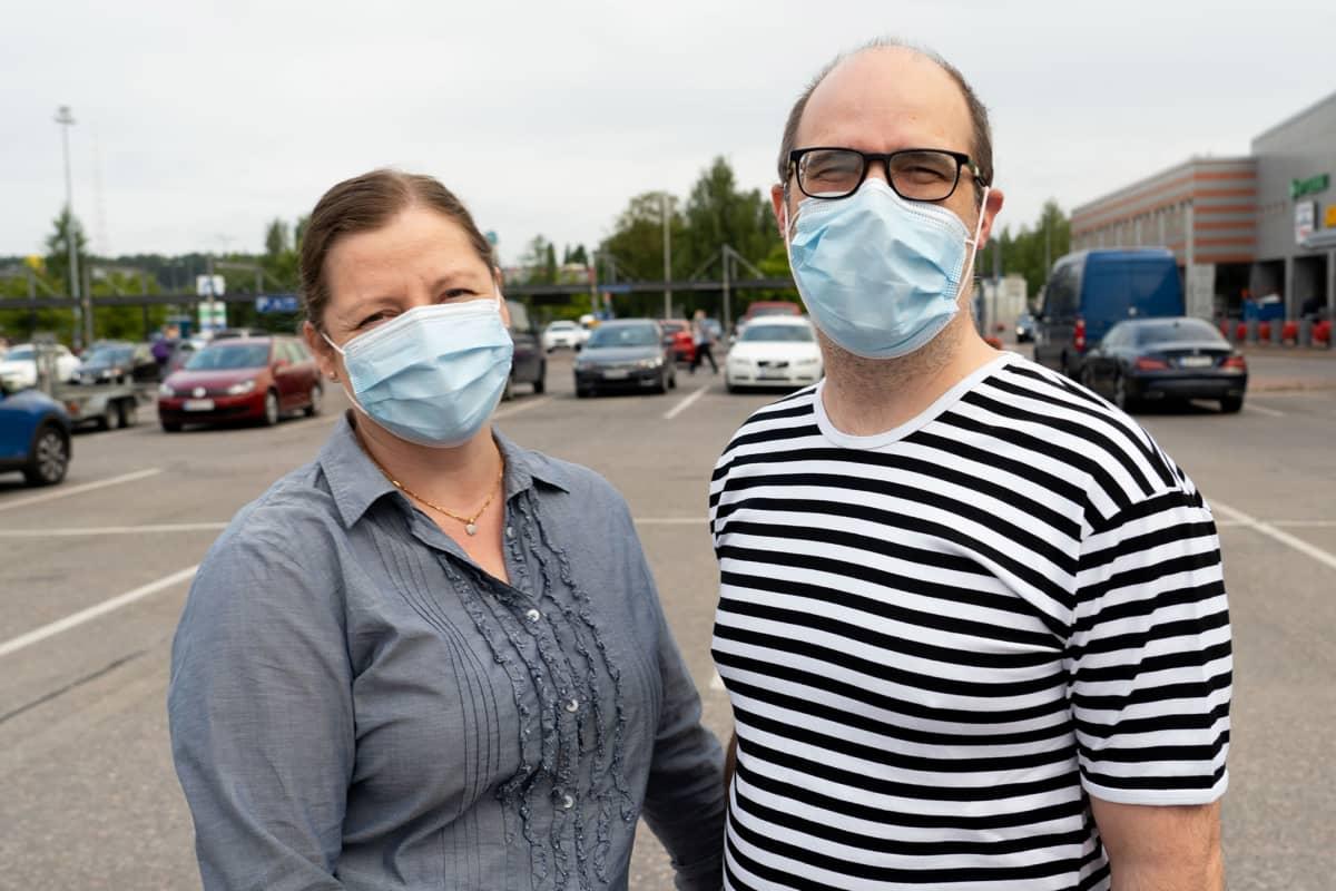 nainen ja mies kauppakeskuksen parkkipaikalla, maskit molemmilla päässä