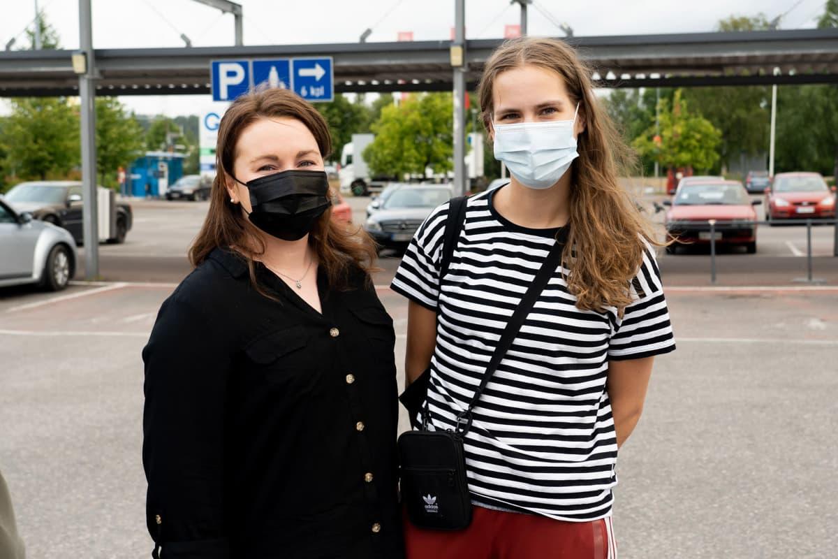 Pitkähiuksiset nuorehkot naiset kauppakeskuksen edessä, molemmilla maski kasvoilla