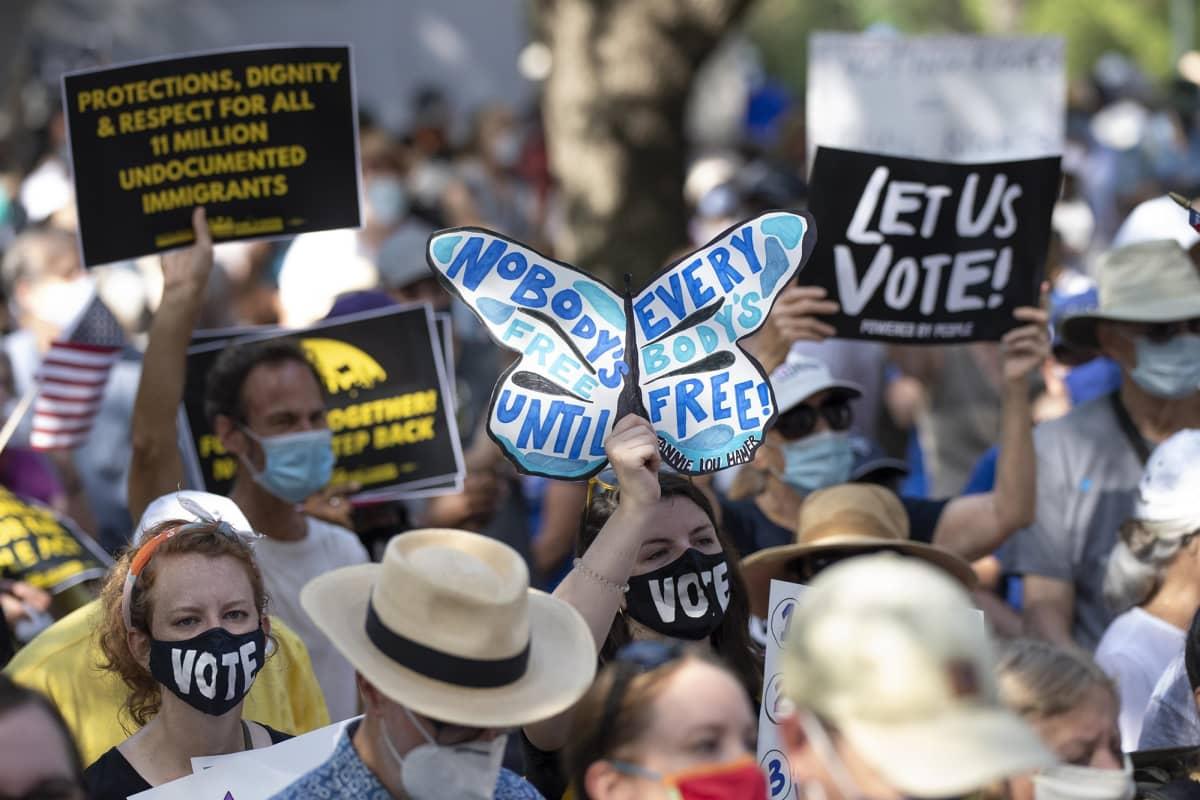 Austinissa ihmisiä marssimassa äänetysoikeuksien puolesta.