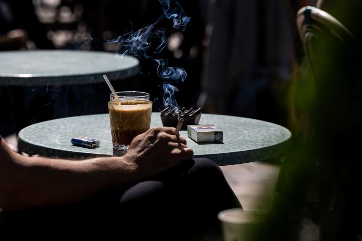 Anonyymi ihminen juo kahvia ja polttaa tupakkaa aurinkoisella terassilla.