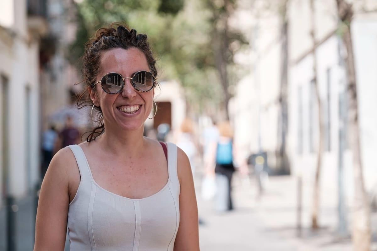 Kuvaa Barcelonan kaduilta. Nainen katsoo kameraan ja hymyilee.