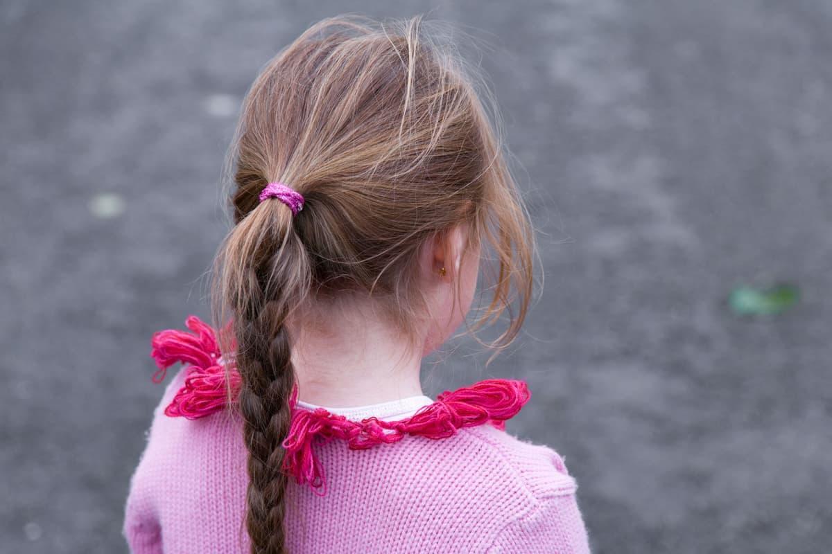 Nuori tyttö takaapäin kuvattuna.