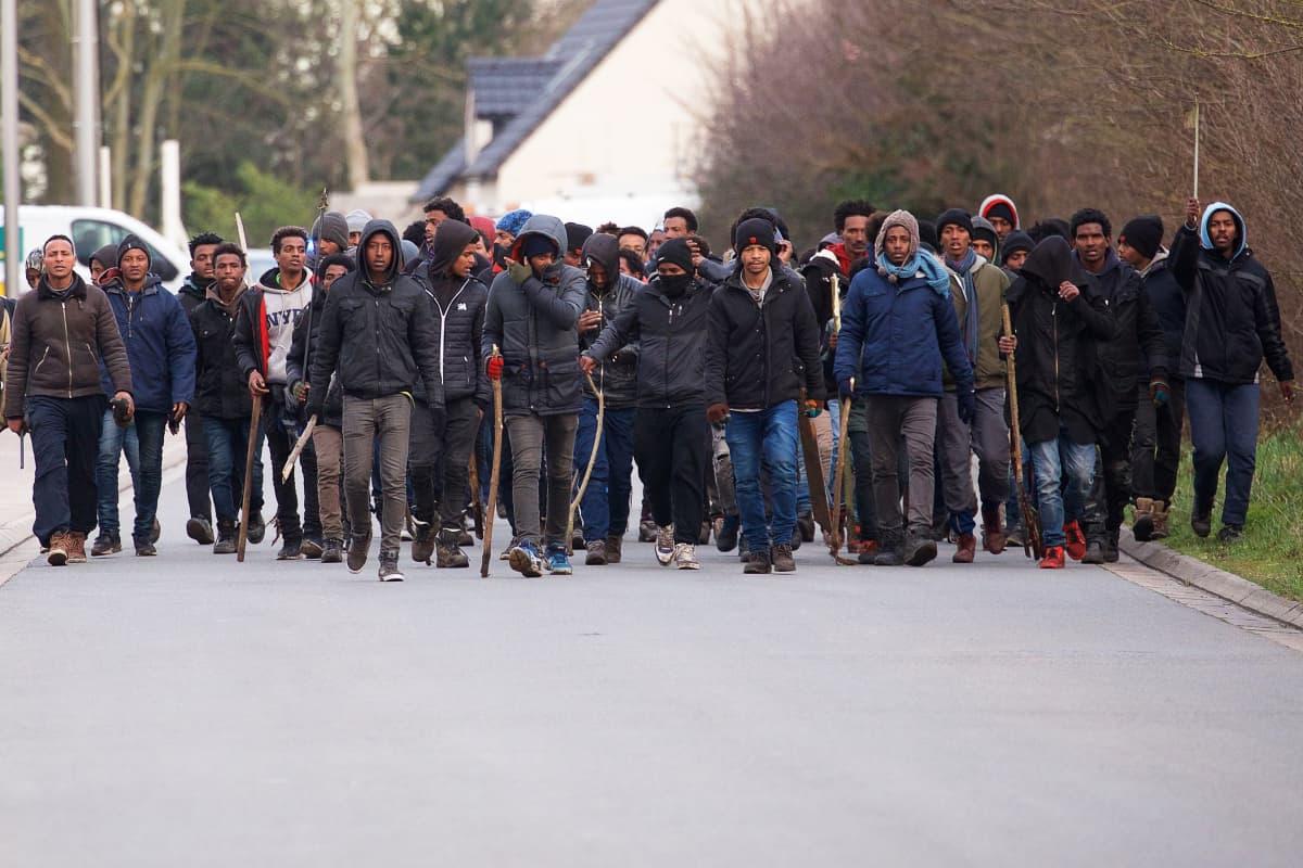 Kuvassa siirtolaismiesten joukko kepit käsissään, valmiina hyökkäämään.