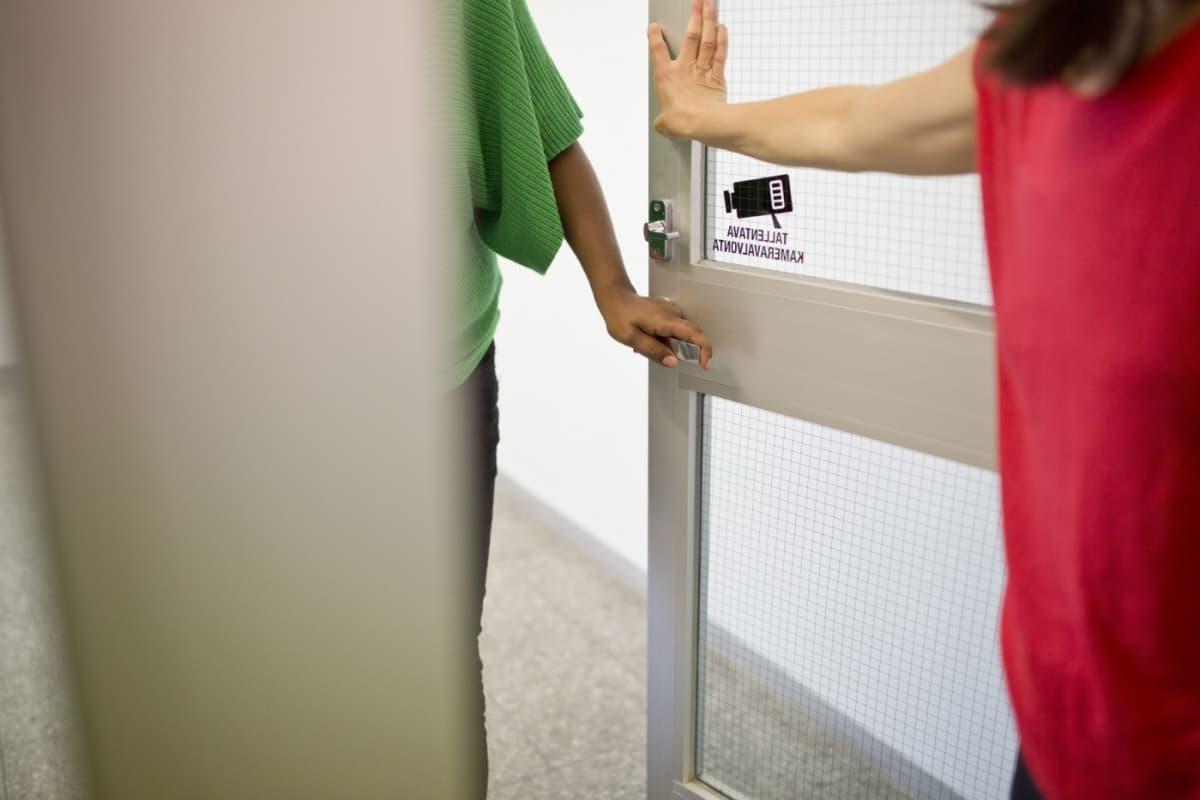 Nainen aukaisee ovea toiselle naiselle.