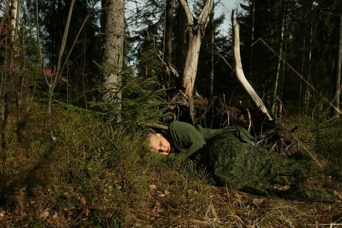 Anneli Jauhiainen makaa metsässä