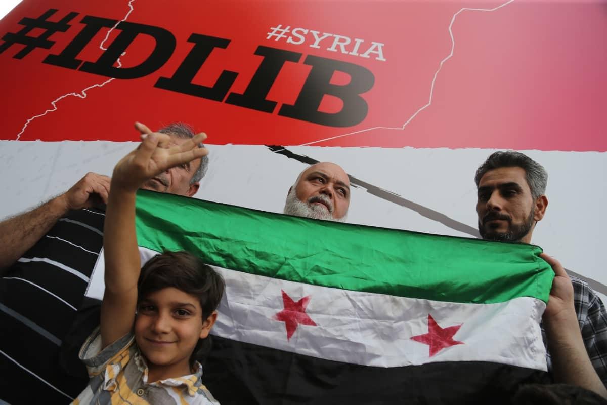 Ihmisiä Vapaan Syyrian lipun edessä, takana Idlib-kyltti