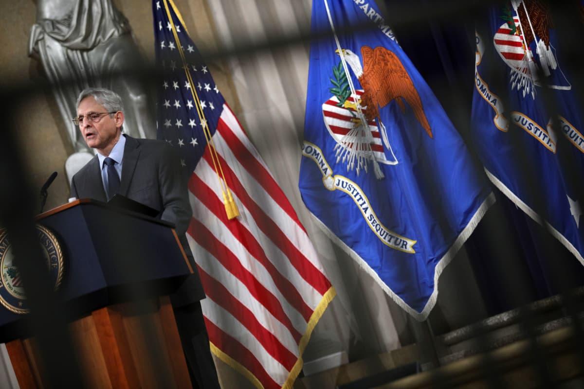 Yhdysvaltain oikeusministeri Merrick Garland puhuu. Vieressä USA:n lippu ja oikeusministeriön sininen lippu.