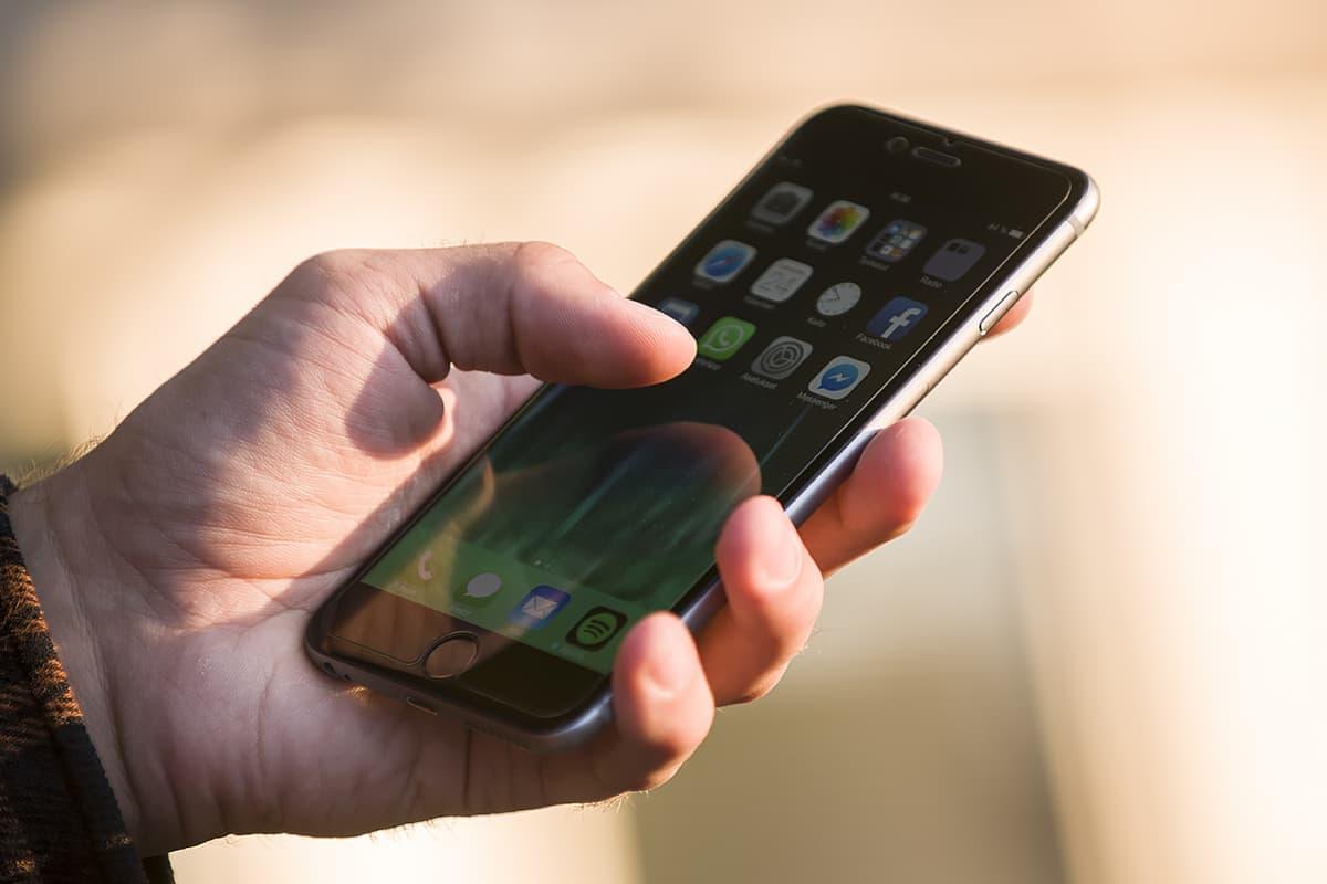 Miehen kädessä älypuhelin jossa näkyy sosiaalisen median appseja.