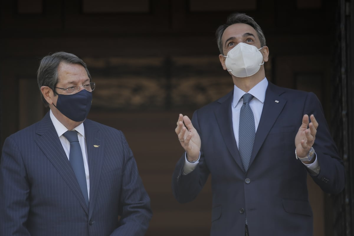 Kaksi miestä maskit päässä, Mitsotakis elehtii käsillään ja katsoo ylöspäin.