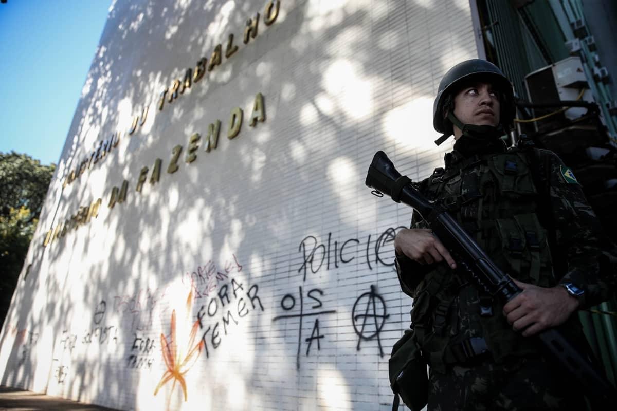 Mies vartioi rakennuksen edustalla aseen kanssa.