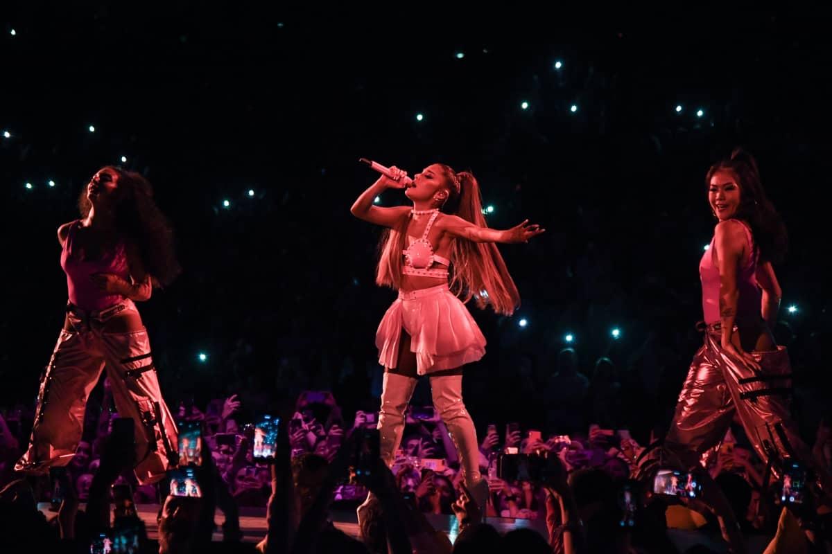 Laulaja Ariana Grande laulaa silmät kiinni lavalla kahden tanssijan ympäröimänä. Hänellä on yllään valkoinen latex-toppi, lyhyt vaalea röyhelöminihame ja korkeat valkoiset latex-saappaat.