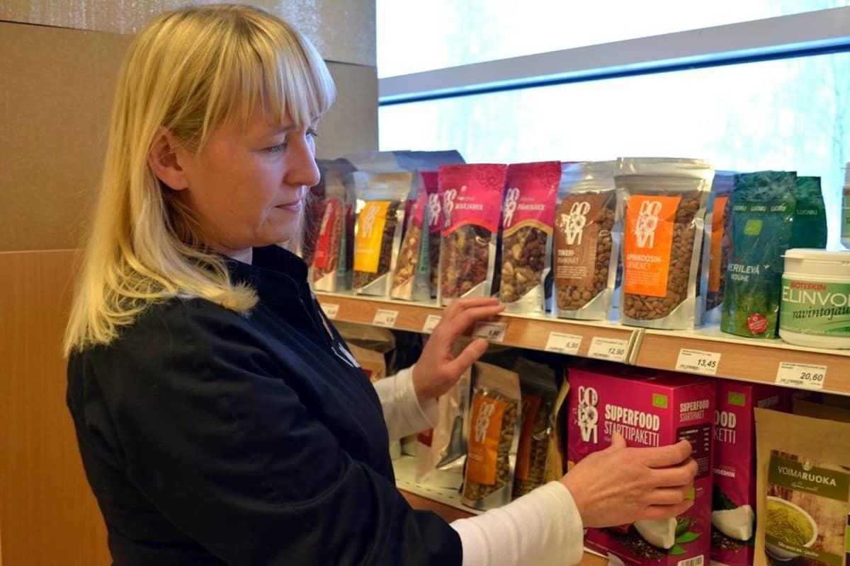Nainen asettelee superfood-pakettia tuotehyllyyn.