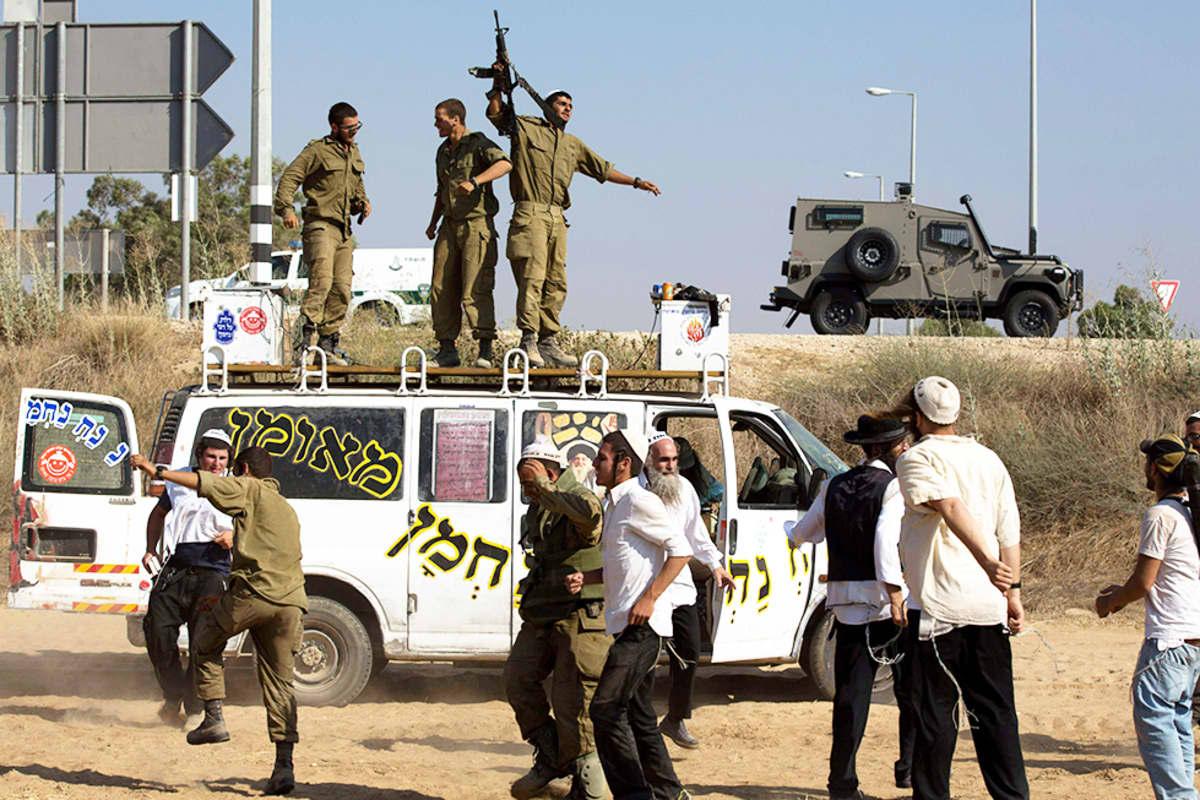 Ryhmä ortodoksijuutalaisia tanssi Israelin sotilaiden kanssa lähellä Gazan rajaa 20. heinäkuuta.
