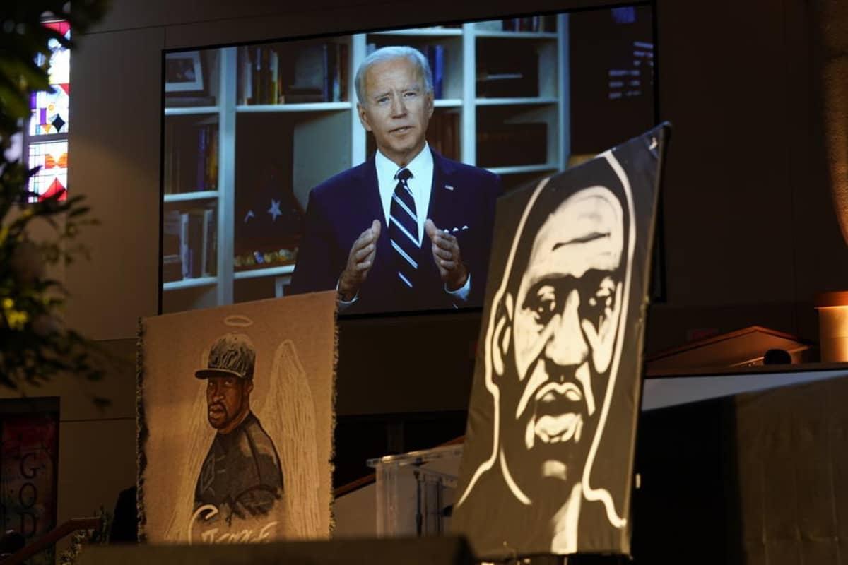 Kuvassa Joe Biden. Hänen edessään on kuva George Floydista.