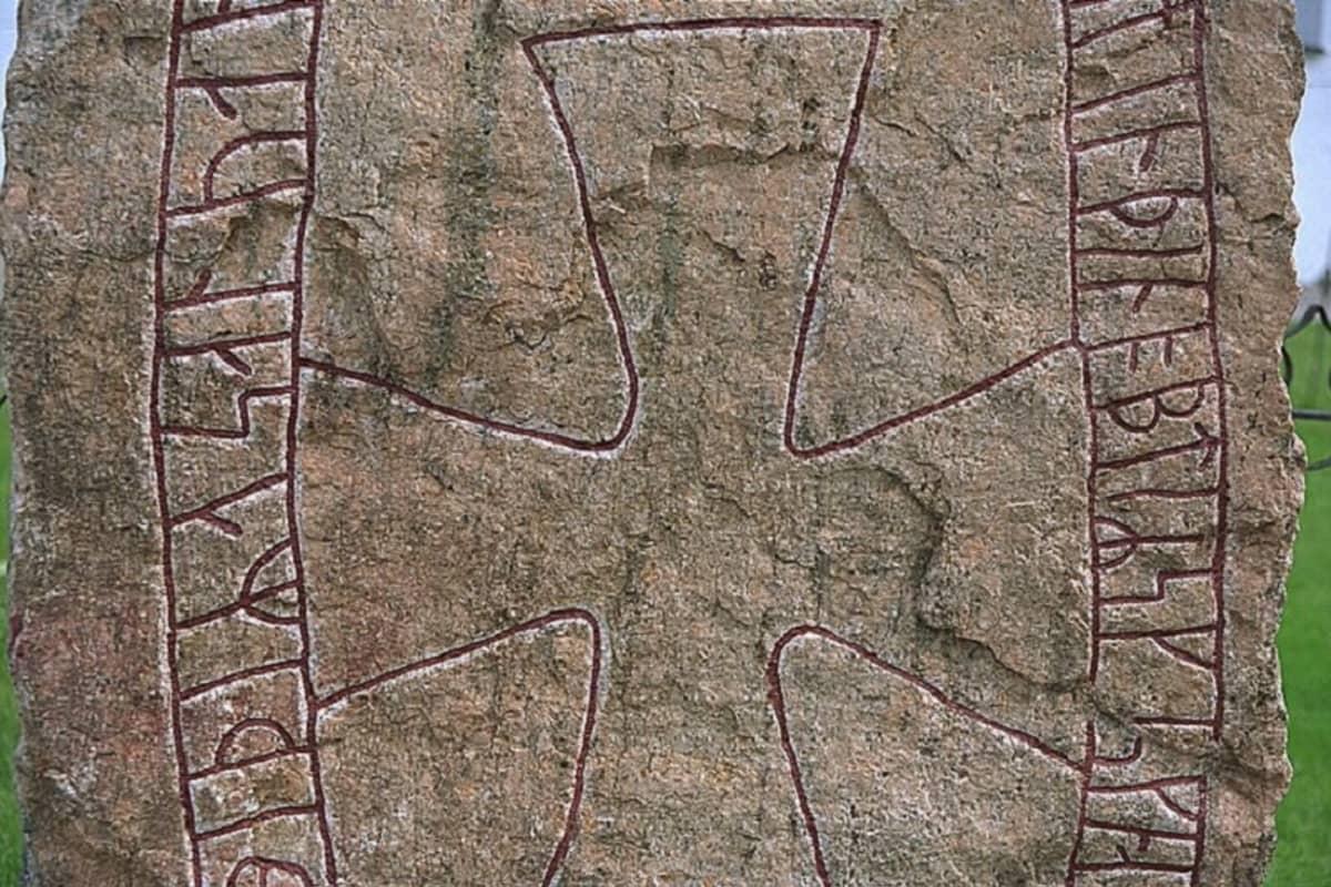 Lähikuva kiveä kiertävästä riimukirjoituksesta ja sen keskellä olevasta suuresta rististä.