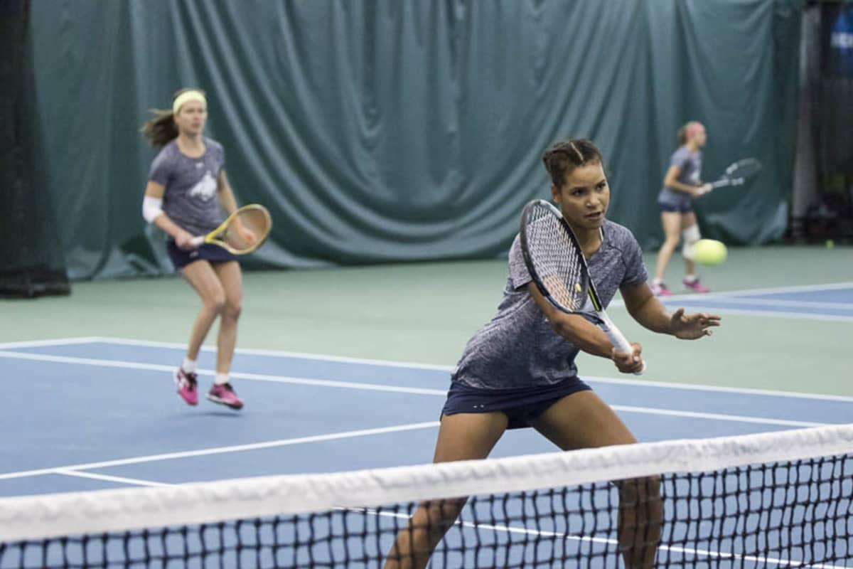 Holopaiset oppivat Yhdysvaltain yliopistourheilupiireissä uudenlaista yhteisöllisyyttä, kun yksinäisen puurtamisen sijaan harjoittelu ja kilpailumatkat tapahtui tiimeissä. Kuvassa Naomi Holopainen ja hollantilaissyntyinen Laura Middle nelinpelissä 2016.