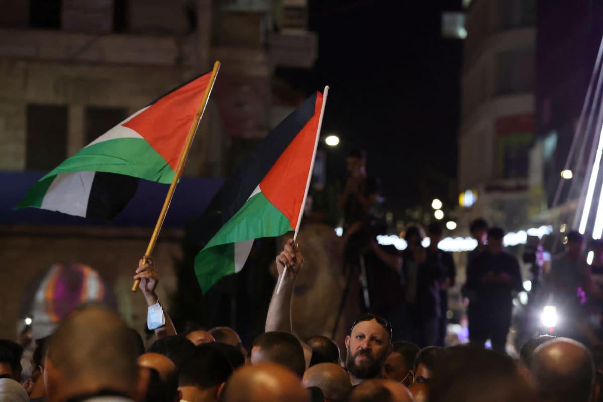 Ihmiset heiluttavat palestiinalaisten lippuja öisellä kadulla