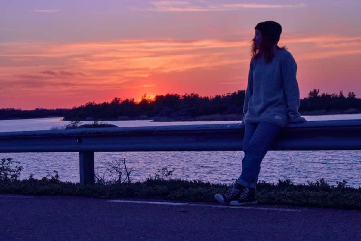 Johanna Rita nojaa autotien kaiteeseen ja katselee auringonlaskuun