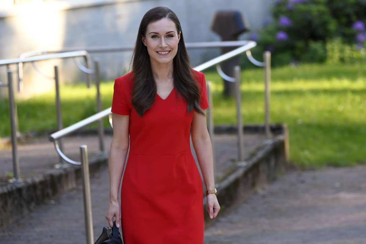 Statsminister Sanna Marin (SDP) på väg till Yles Studiohus för valdebatt. Hon ler och har en röd klänning på sig.