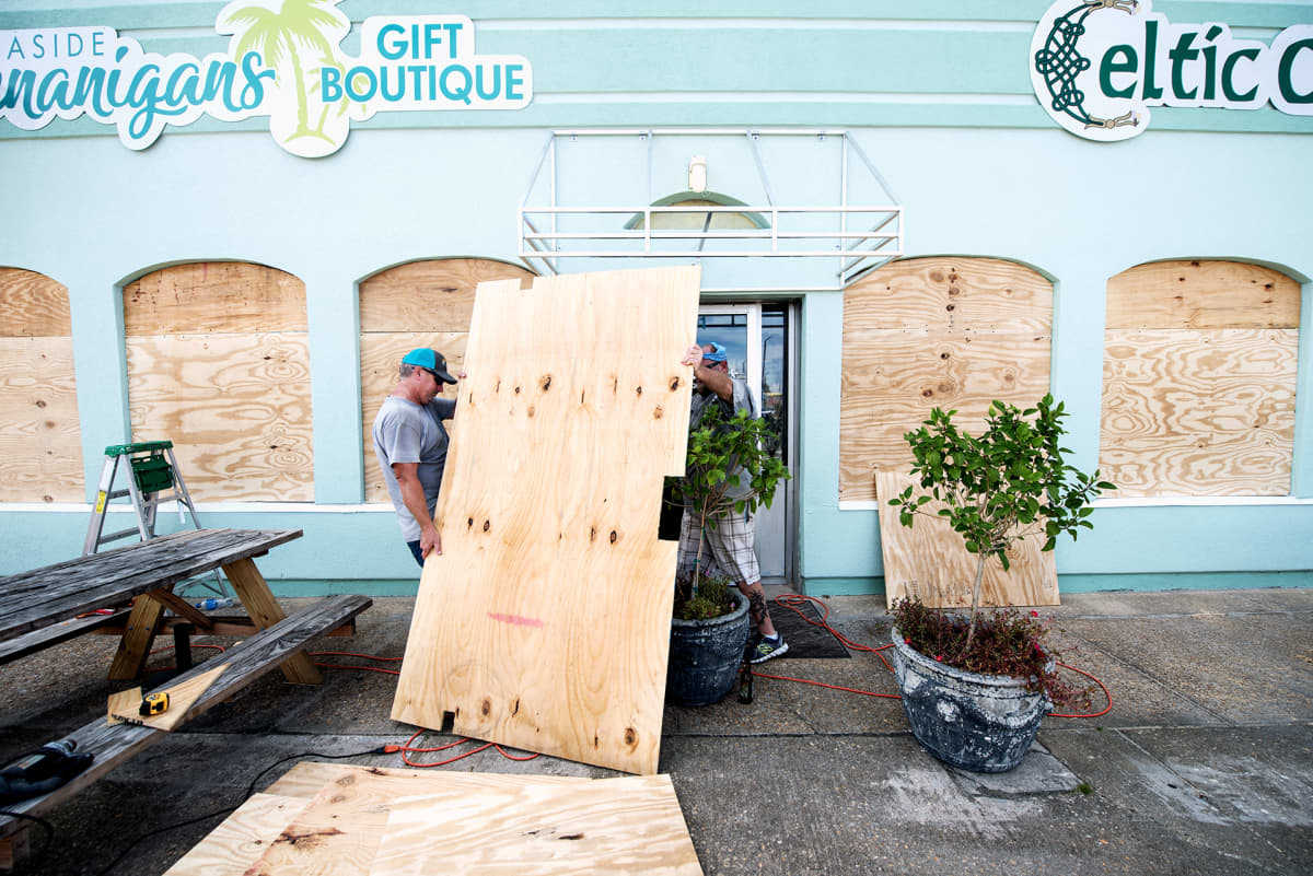Jeff Hogan (vas) ja Rob Warner suojaavat liikkeensä ikkunoita vanerilevyillä Pohjois-Carolinan rannikolla
