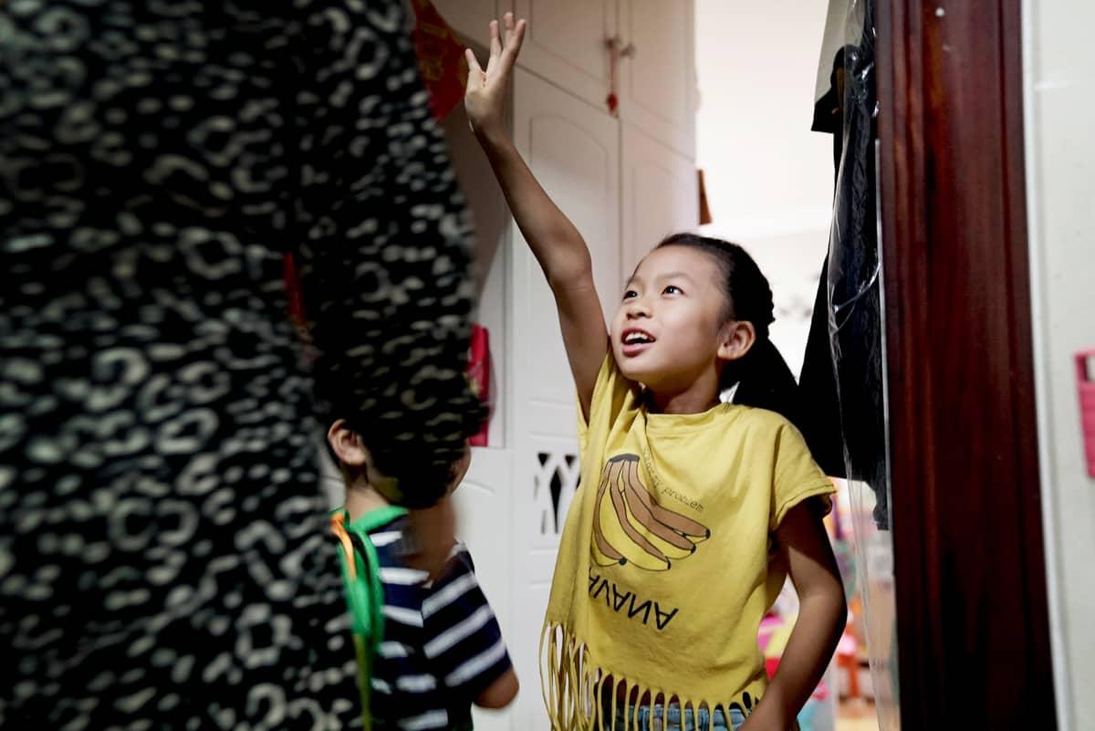 Qiqi kiirehtii ovelle äitiään Xia Huita ja pikkuveljeään Xiangxiangia vastaan, kun he tulevat kotiin päiväkodista.