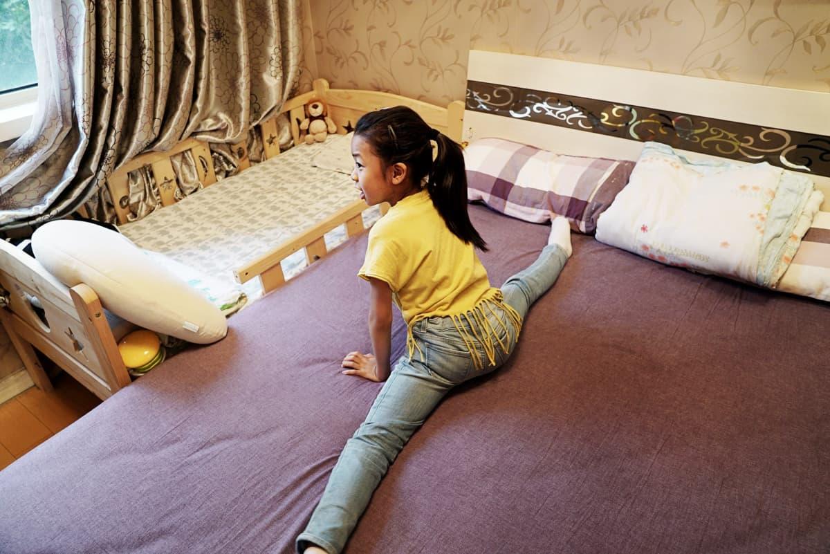 Qiqi taipuu spagaattiin vanhempiensa sängyllä. Vieressä on pikkuveljen sänky.