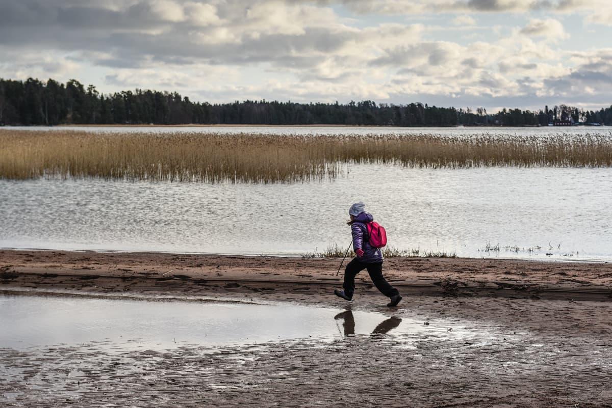 Lapsi juoksee rannalla.