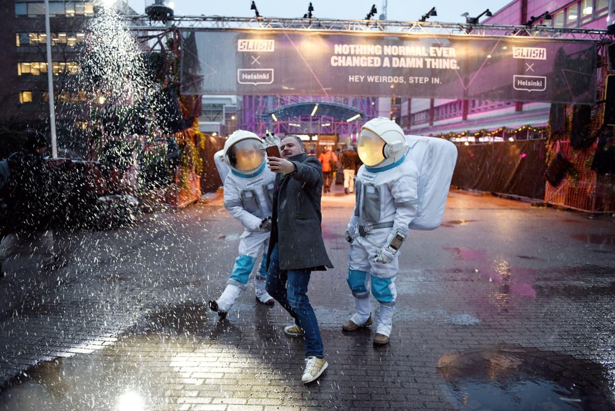 Slushiin matkalla oleva messuvieras ottaa valokuvia lumipyryssä messukeskuksen edustalla.
