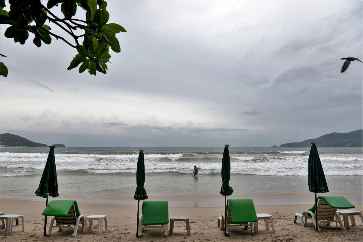 Joukko rantatuoleja seisoo melko tyhjällä rannalla. Vedessä rannalla seisoo yksi ihminen.